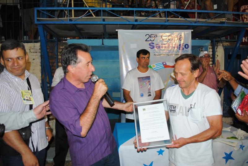 Na foto, em 2013, Valdeci entrega placa da Lei de sua autoria que inclui a Copa Santiago no Calendário Oficial de Eventos do Estado.